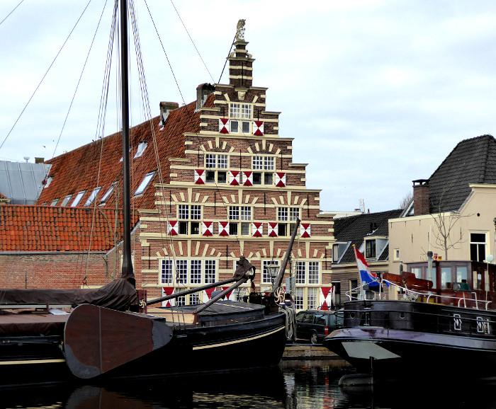Foto van gracht en gebouw met trapgevel en luiken