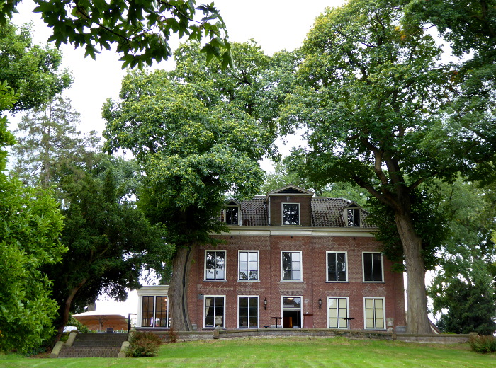 Foto van buitenhuis tussen bomen