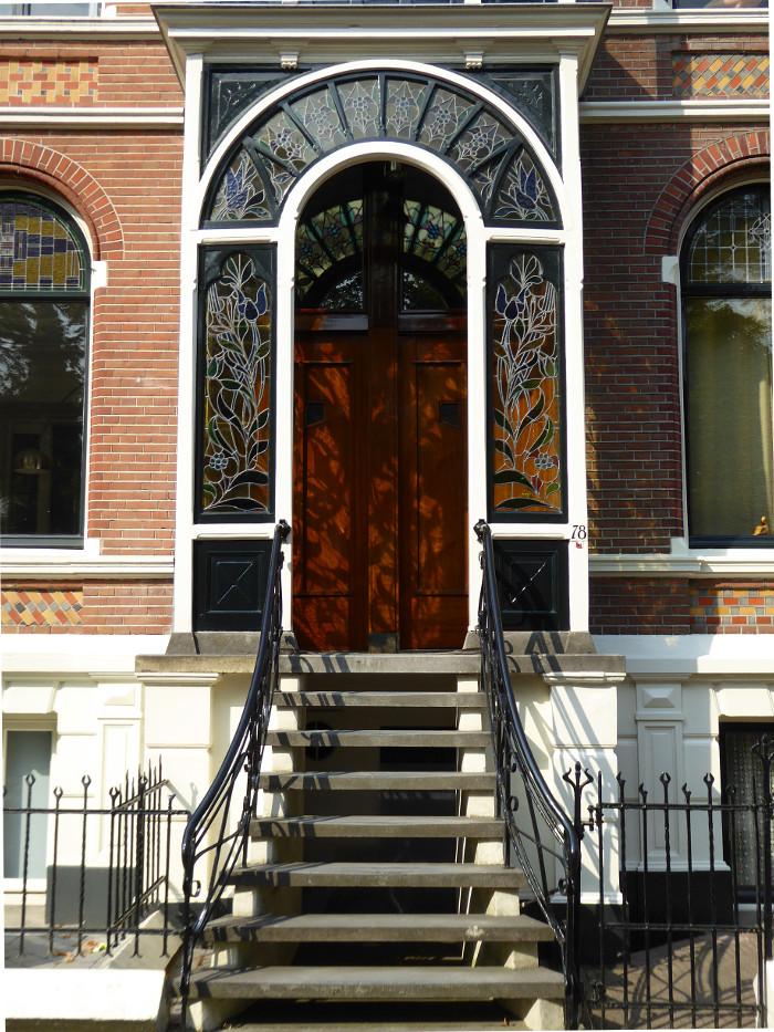 Foto van trap naar bordes met glas in lood portiek
