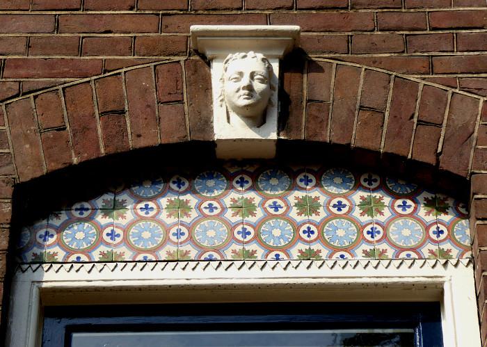 Foto van decoratie boven raam met beeldje van hoofd