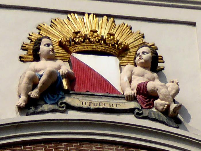 Foto van decoratie aan gevel met wapen van Utrecht en engeltjes.