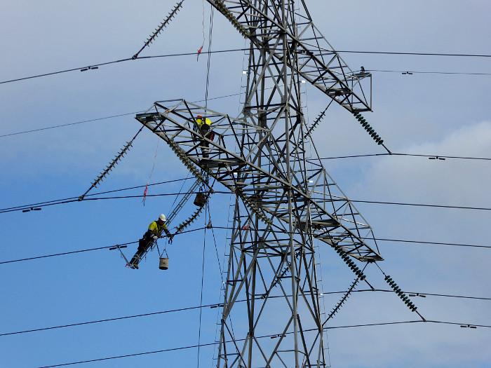 Foto van arbeiders in hoogspanningsmast