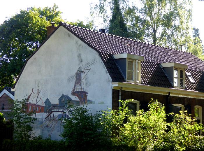 Foto van huis met muurschildering van landschap met molen