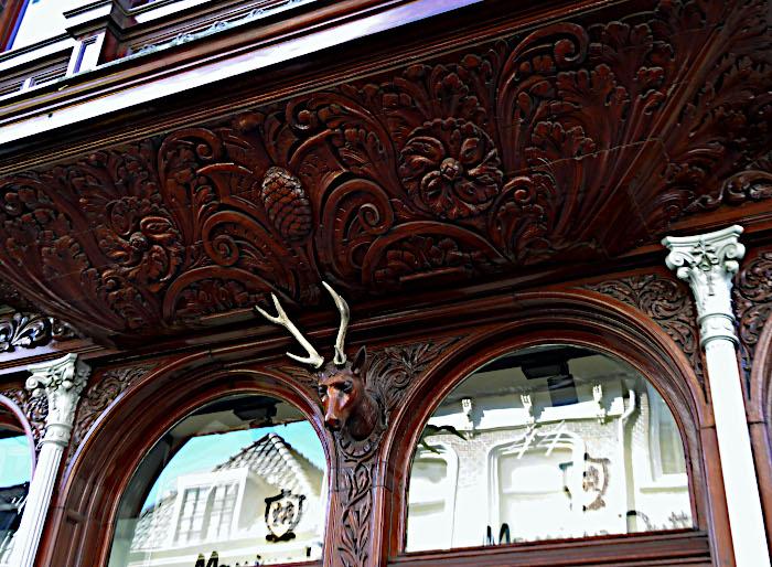 Foto van gevel met houtsnijwerk met hertenkop