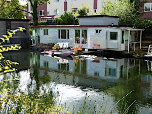 Foto van woonboot met terras en roeiboot
