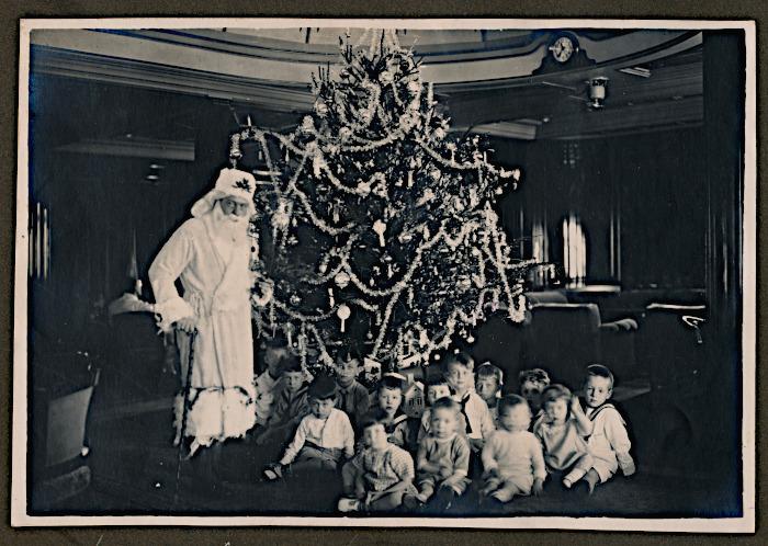 Foto van kinderen met kerstman bij kerstboom
