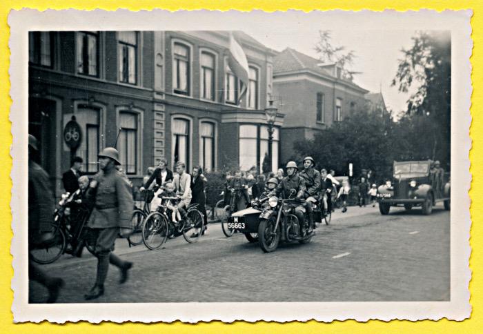 Foto van militaire motor met zijspan en open auto