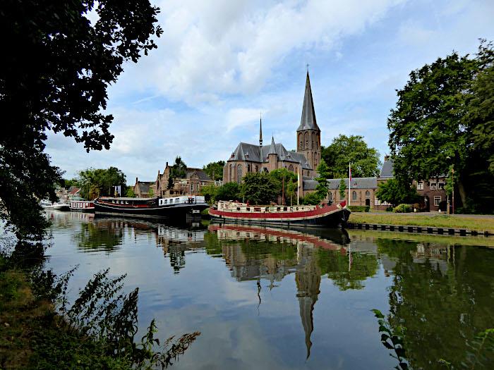 Foto van kanaal met boten en kerk