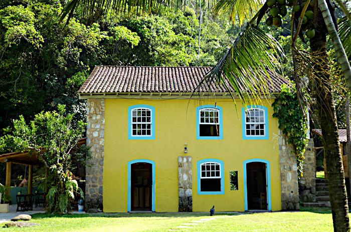 Foto van geel huis met blauwe ramen in het groen