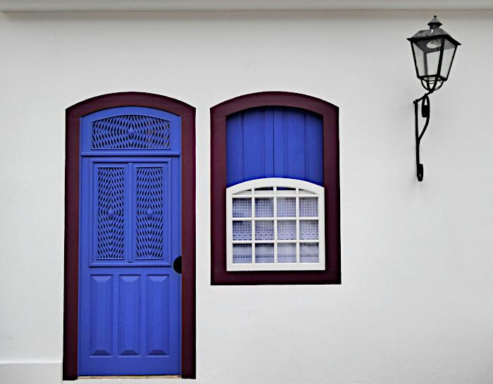 Foto van blauwe deur, bauw raam en lantaarn aan muur