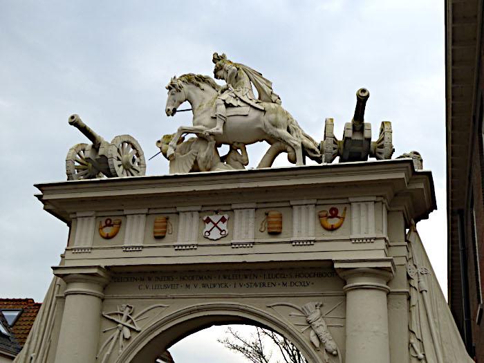 Foto van bovenkant poort met ruiter en kanonnen