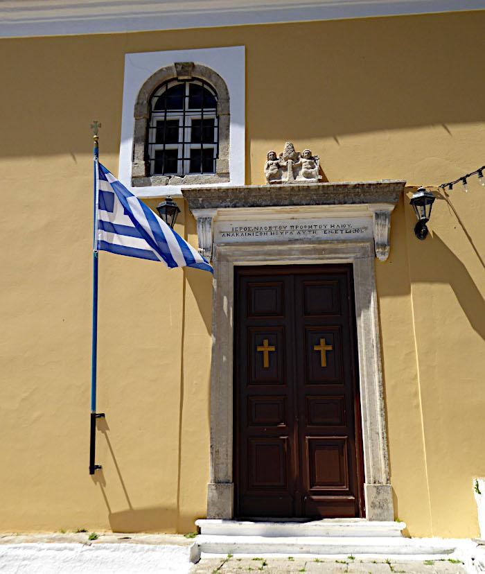 Foto van deur van kerk en Griekse vlag