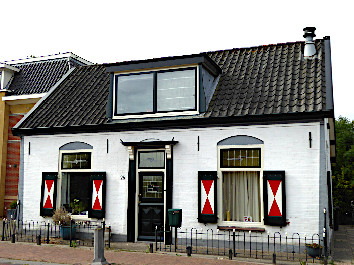 Foto van wit huis met rood-witte luiken