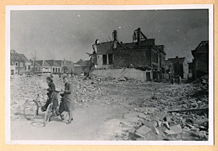 Foto van twee fietsers bij verwoeste huizen