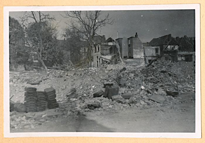 Foto van stapel jerrycans bij bomkrater en verwoeste huizen