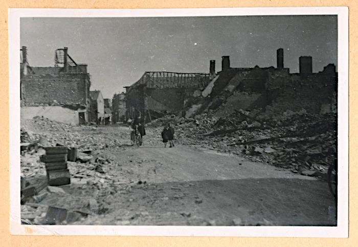 Foto van volwassene en kinderen in verwoeste straat