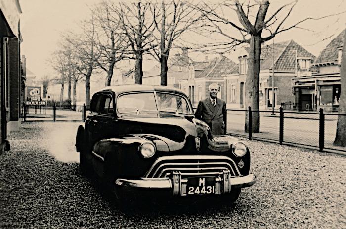 Foto van man bij oude auto