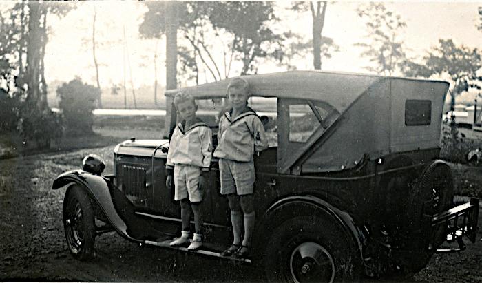 Foto van twee kinderen op treeplank van oude auto