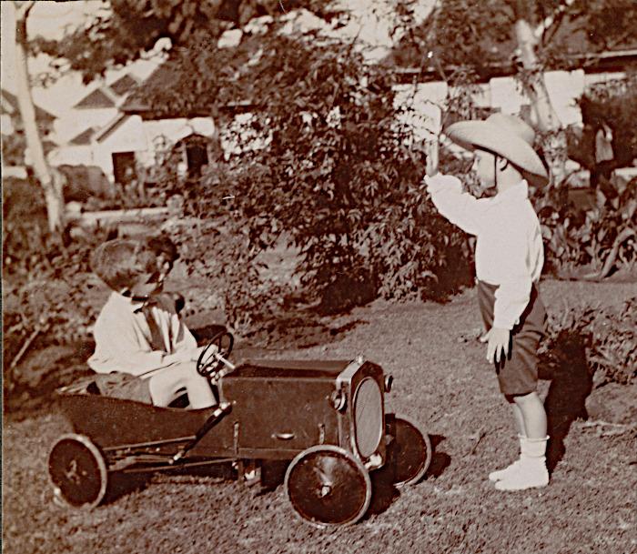 Foto van kinderen in tuin met trapauto
