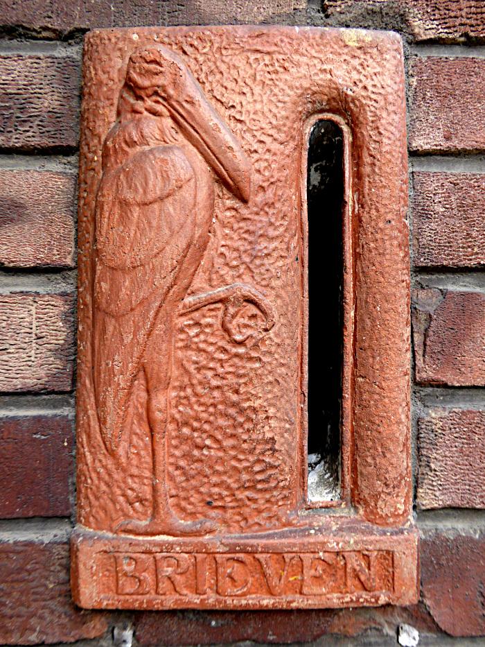 Foto van brievenbus met relief van vogel