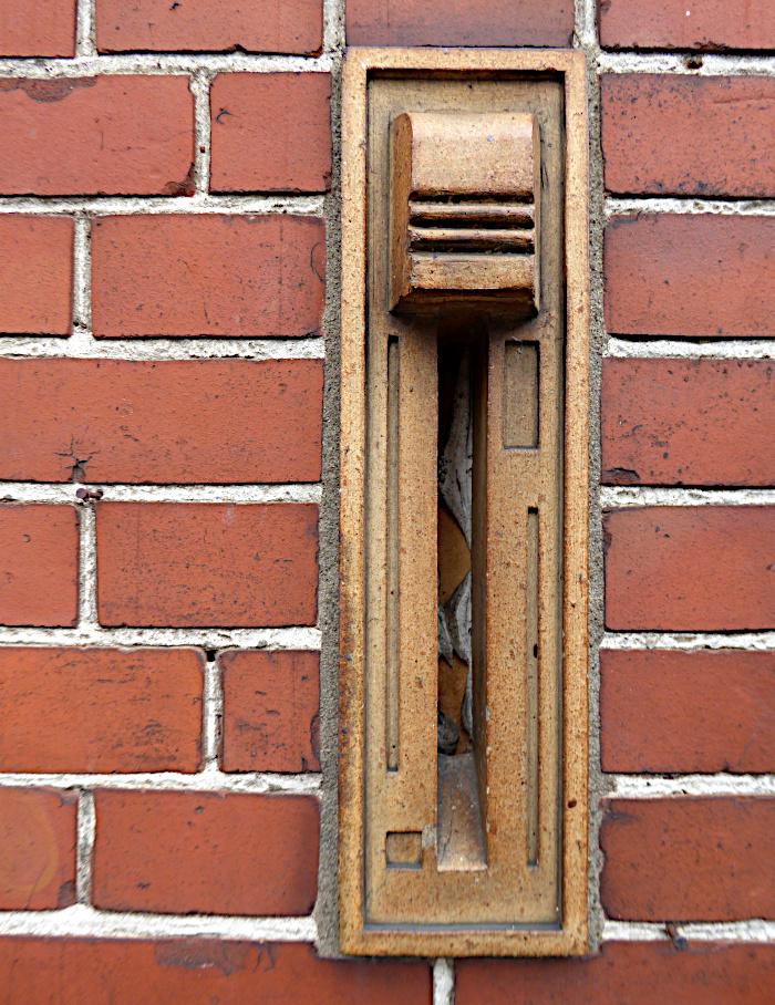 Foto van in muur gemetselde aardewerken brievenbus