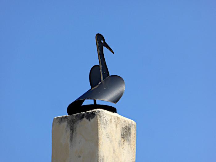 Foto van kap op schoorsteen in vorm van vogel