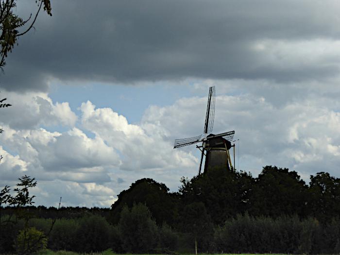 Foto van molen onder donkere wolk