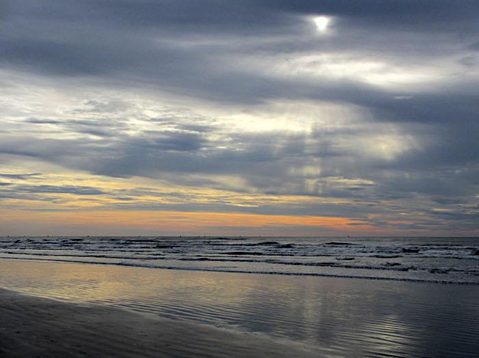 Foto van zon achter wolken boven zee
