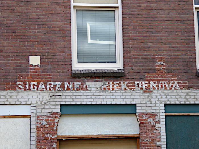 Foto van resten opschrift op muur: Sigarenfabriek Denova