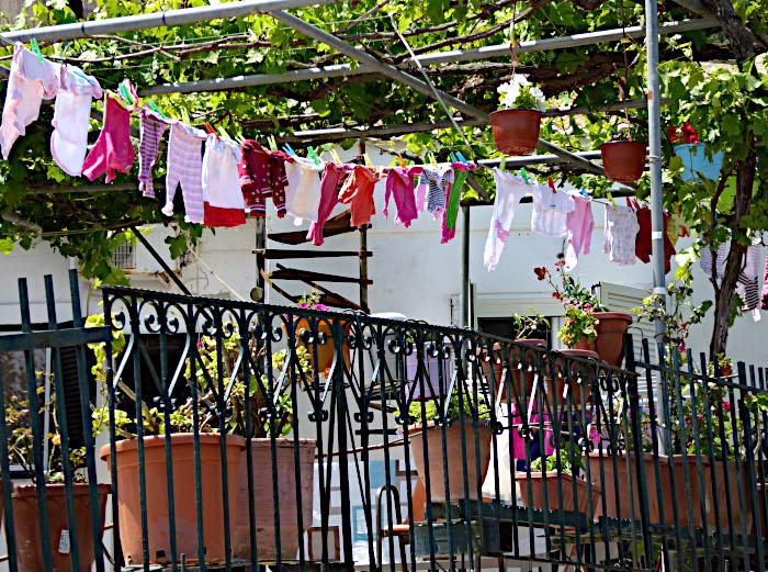 Foto van waslijn met wasgoed onder begroeide pergola