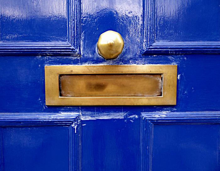 Foto van metalen brievenbus in houten deur