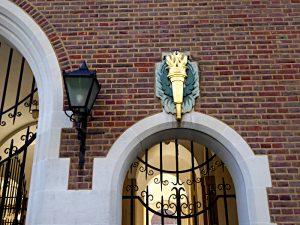 Foto van lamp en verguld relief (fakkel) aan muur