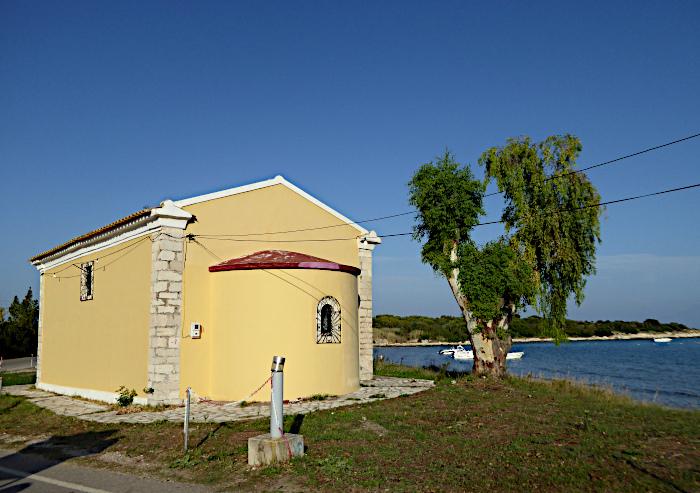 Foto van geel kerkje naast boom