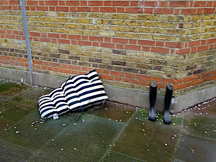 Foto van laarzen en stoelkussen bij muur