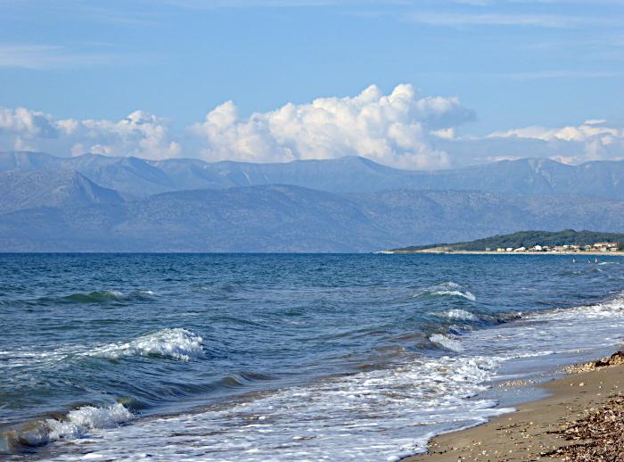 Foto van strand, zee, bergen, wolken