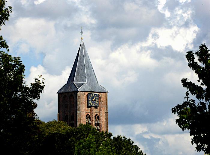 Foto van kerktorentop boven groen