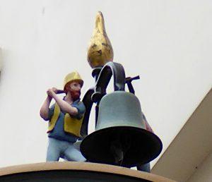 Foto van detail klok met man die met hamer op klok slaat