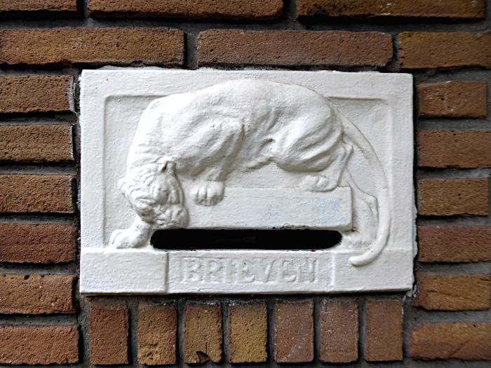 Foto van stenen brievenbus met relief van katachtige
