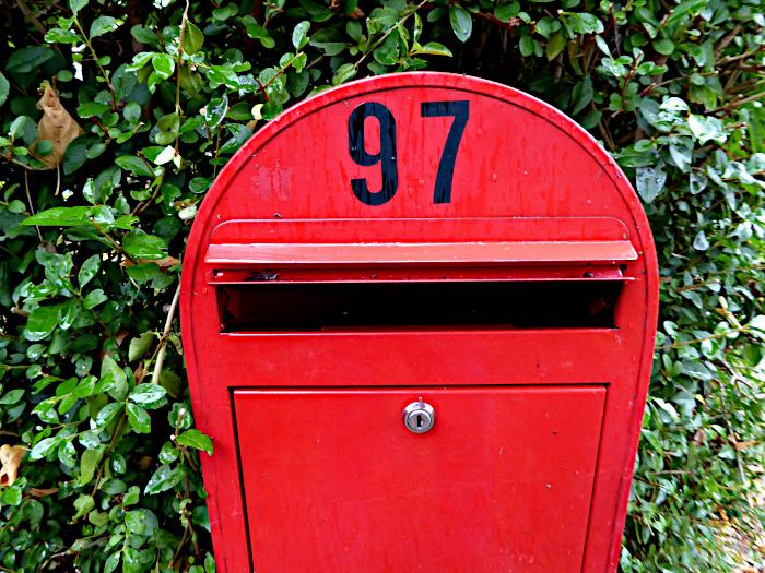Foto van rode brievenbus in het groen