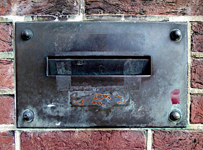 Foto van metalen brievenbus in bakstenen muur