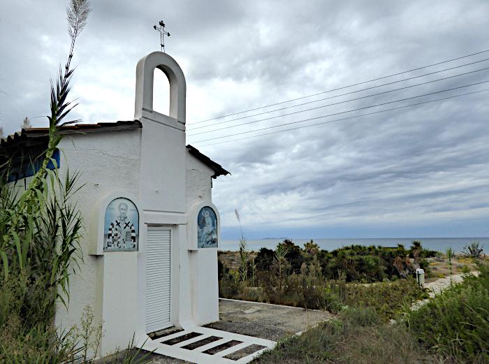 Foto van kapel bij zee onder wolkenlucht