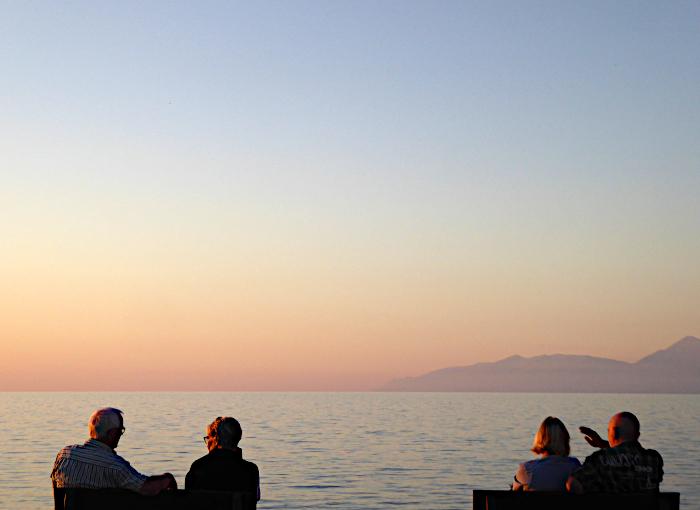 Foto van twee paren bij zonsondergang aan zee