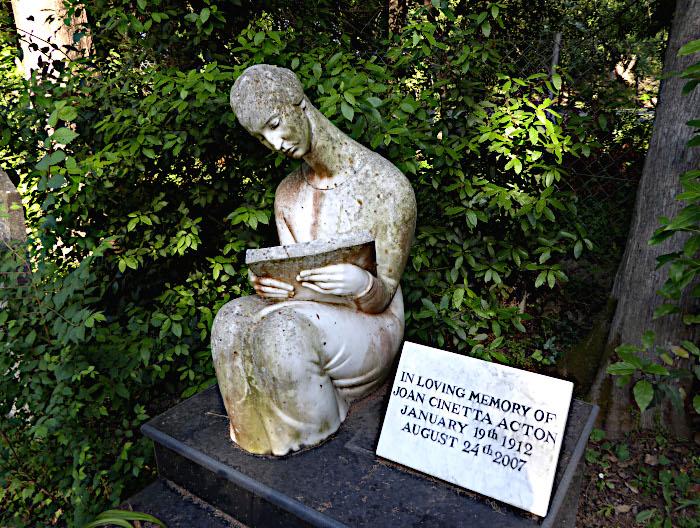 Foto van graf met beeld van lezende dame