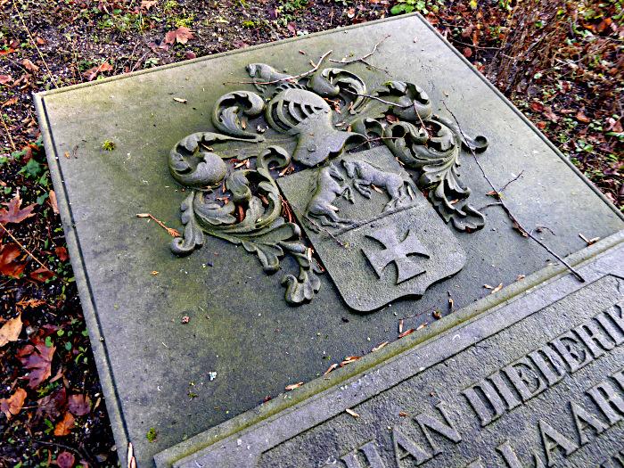 Foto van detail grafsteen met afbeelding van ridderhelm en wapen