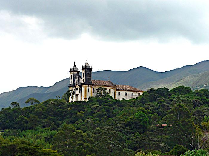 Foto van kerk tussen groen op heuveltop
