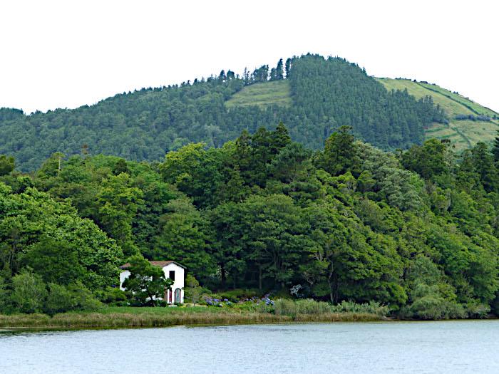 Foto van huisje tussen meer en bomen