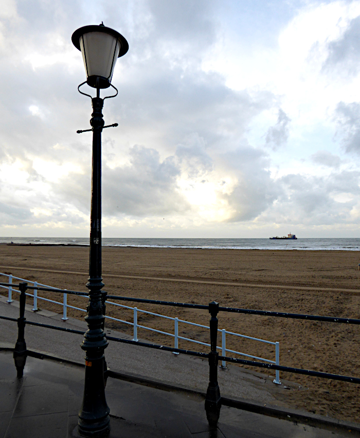Foto van lantaarn op boulevard, strand, zee en wolken