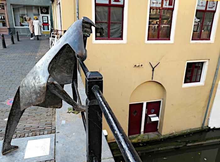 Foto van beeld van man leunend op brugleuning