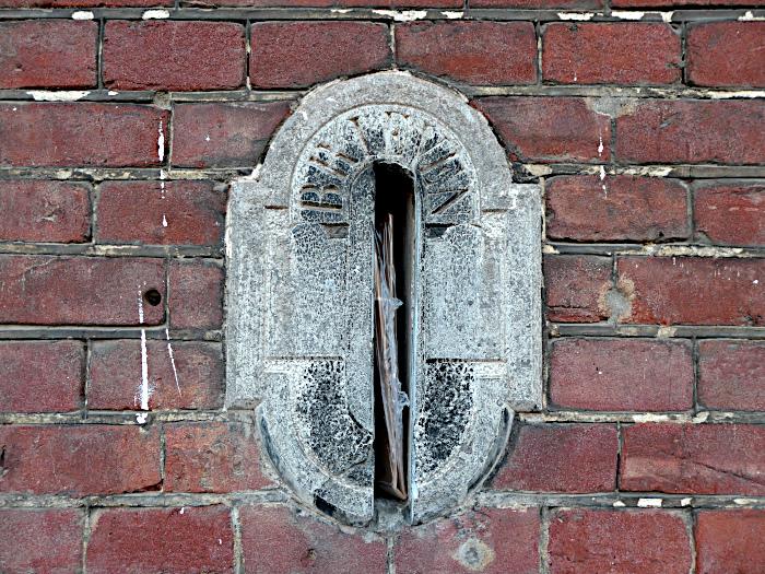 Foto van stenen brievenbus in bakstenen muur