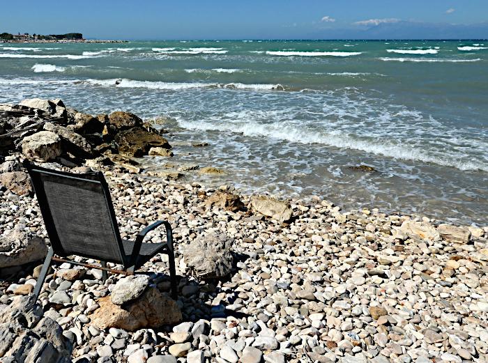 Foto van stoel met drie poten leunend op rotsblok op kiezelstrand